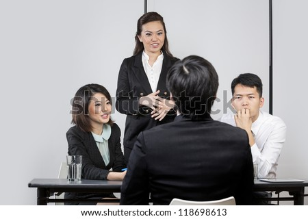 Panel of Chinese colleagues from hr department interview a male applicant.