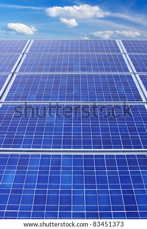 Panels of solar collection cells fade towards a bright blue sky with white clouds vertical - stock photo