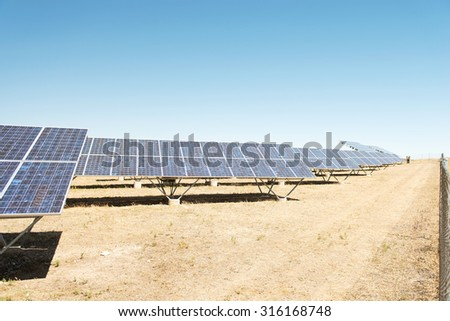 Panels of solar power station on the field. - stock photo