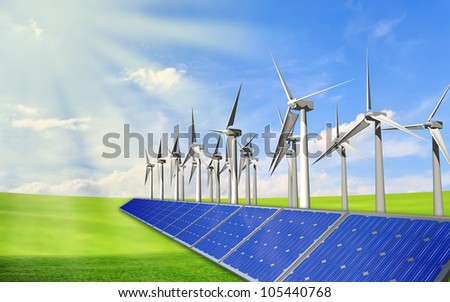 Panels with solar cells and wind generators on a green field with blue sky