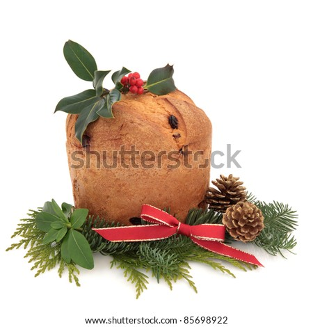 Panettone christmas cake  decorated with holly berry leaf sprig, blue spruce, pine cones and red ribbon isolated over white background.