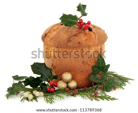 Panettone christmas cake with floral decoration of holly, ivy, mistletoe and cedar cypress leaf sprigs with pine cones and gold bauble cluster over white background.