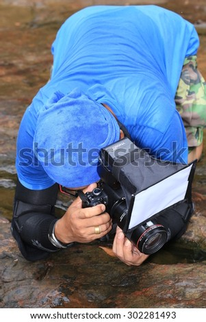PANG SIDA NATIONAL PARK, Thailand :July 25, 2015: An insect photographer taking shots lyning on the rock in Pangsida, Thai National Park
