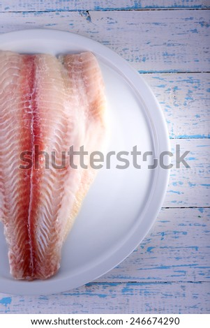 Pangasius fillet on plate and color wooden table background - stock photo