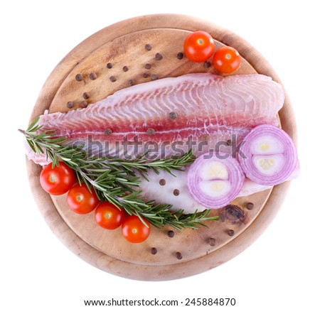 Pangasius fillet on wooden cutting board with cherry tomatoes and spices isolated on white - stock photo