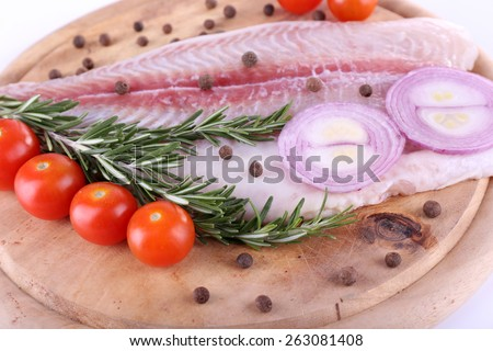 Pangasius fillet on wooden cutting board with cherry tomatoes and spices on qhite background - stock photo