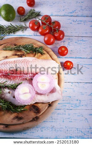 Pangasius fillet with herb, spices and vegetables on cutting board and color wooden table background - stock photo