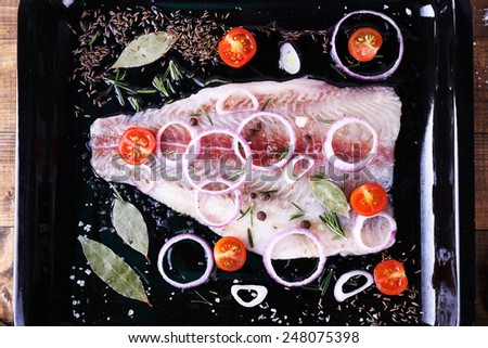 Pangasius fillet with spices and vegetables on firepan and wooden table background - stock photo