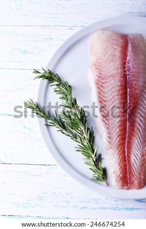 Pangasius fillet with sprigs of rosemary on plate and color wooden table background - stock photo