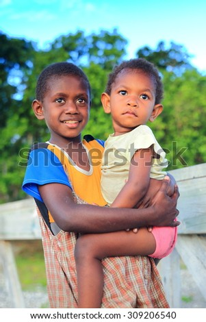 PANGI,VANUATU-OCTOBER 14, 2014: Native girl takes care of her brother while their parents work in a local business on October 14, in Pentecostes-Vanuatu.