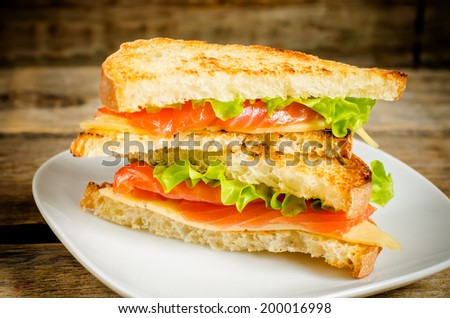 panini sandwiches with salmon, cheese and salad on a dark wood background. toning. - stock photo