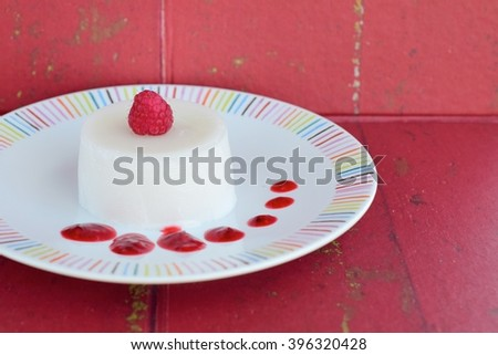 Panna cotta with raspberry sauce on red background - stock photo