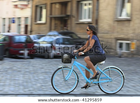 Panning image of a young woman riding her bicycle in a traditional city square. - stock photo