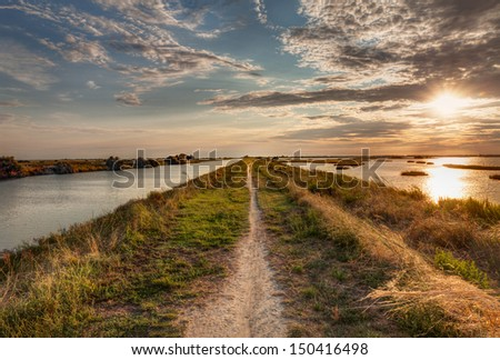 "panorama at sunset of the wetland, a long straight path across the lagoon in the natural reserve ""Valli di Comacchio"" in Italy - stock photo"
