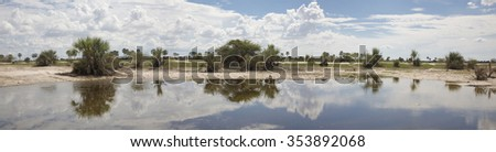 Panorama clouds and landscape and its reflection in a small water pond, Kaokoland, Namibia - stock photo