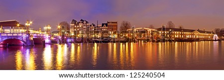 Panorama from Amsterdam innercity with the Amstel in the Netherlands by night - stock photo