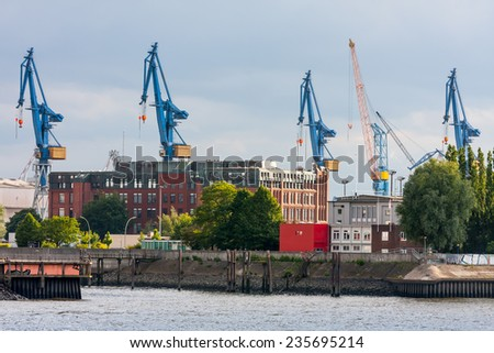 Panorama harbor cranes in Hamburg. Panorama with blue port cranes in the port of Hamburg - stock photo