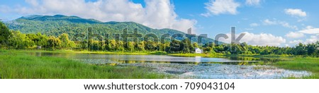 panorama image of beauty sunny day on the lake with green mountain after rain in spring season.