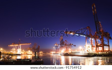 Panorama image of the illuminated cargo port in Hamburg at night with container terminals, cargo ships and cranes and a clear blue sky. - stock photo