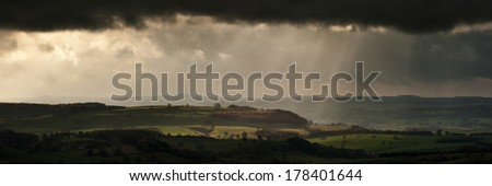 Panorama landscape dramatic sky with sun beams over countryside during Autumn - stock photo