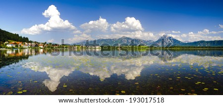panorama landscape in Bavaria at lake Hopfensee with alps mountains - stock photo
