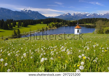 panorama landscape in Bavaria with alps mountains, lake, meadow and little chapel - stock photo