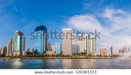 panorama modern building under the blue sky and cloudy with reflection on lake, image concept two-tone warm and cool