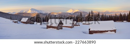 Panorama mountain village of shepherds. Winter landscape with wooden houses. Beautiful Dawn frosty morning. Carpathians, Ukraine - stock photo