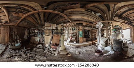 Panorama of a dirty wooden garage full of old obsolete stuff - stock photo