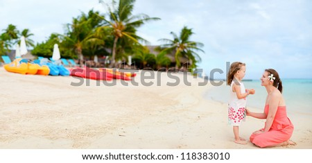 Panorama of a of happy mother and daughter at beach resort - stock photo