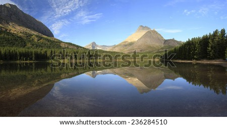 Panorama of a Perfect Reflection on Fishercap Lake Glacier National Park, Montana - stock photo