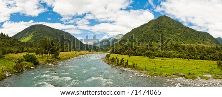 Panorama of a river flowing through a valley - stock photo