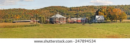Panorama of a round barn on a dairy farm with house and cornfields in Vermont surrounded by colorful Autumn foliage on the nearby hillsides. Time of day is late afternoon with warm light. - stock photo