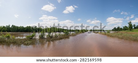 Panorama of a rural road completely inundated with flood waters, with pasture land on the left under water after heavy rains - stock photo