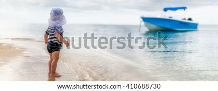 Panorama of a toddler at the beach starring at a blue boat - stock photo