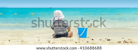 Panorama of a toddler sitting and playing at the beach with turquoise water in a hot summer day