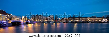"""Panorama of Amsterdam skyline at night, showing the """"skinny bridge"""" and the museum Hermitage along the river Amstel - stock photo"""