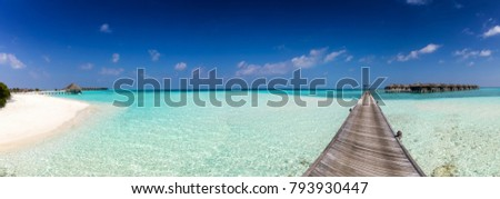 Panorama of an island in the Maldives with a white beach, turquoise waters and a wooden jetty
