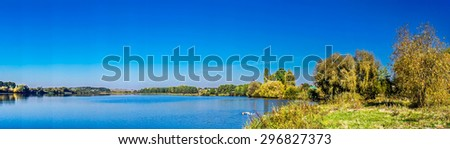 Panorama of autumnal lake and blue sky.