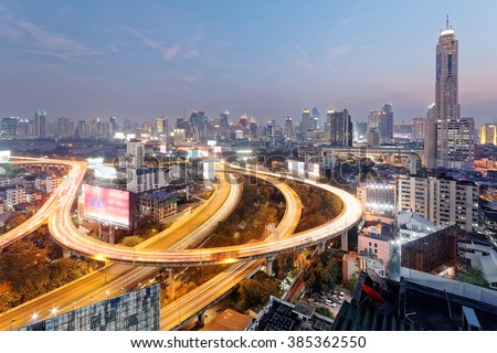 Panorama of Bangkok at dusk with skyscrapers in background and traffic trails on elevated expressways and circular interchanges ~ Bangkok at rush hour with busy traffic on intertwined highway overpass - stock photo
