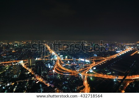 Panorama of Bangkok at dusk with skyscrapers in background and traffic trails on elevated expressways and circular interchanges ~ Bangkok at rush hour with busy traffic on intertwined highway overpass