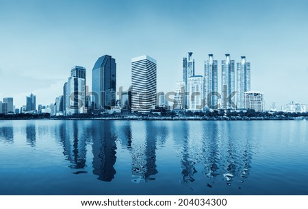 Panorama of bangkok city reflect in river day time blue color tone.