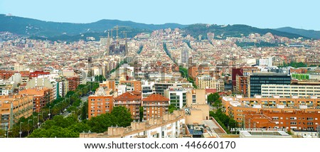 Panorama of Barcelona with houses, streets, a cathedral against mountains.
