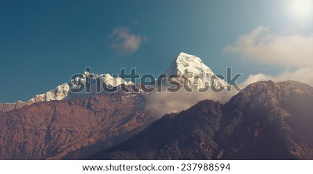 Panorama of beautiful Himalayan mountains after sunrise (sun-effect on upper right corner) - stock photo
