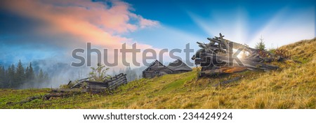 Panorama of beautiful sunrise in a rustic village with broken old wooden houses.  - stock photo