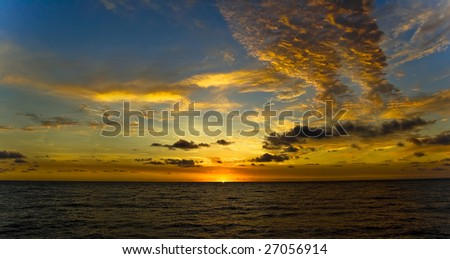 panorama of beautiful sunrise over the ocean with a colorful sky and clouds - stock photo
