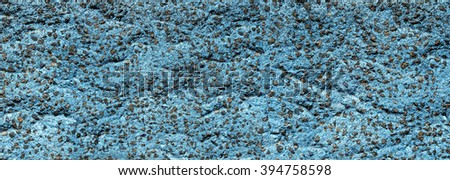 Panorama of blue rough plaster with included small dark stones