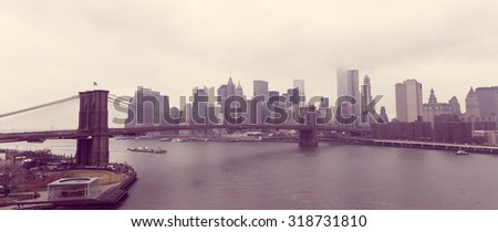 Panorama of Brooklyn Bridge over Hudson River and Downtown Manhattan skyline on a cloudy day