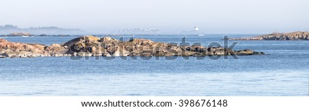 Panorama of coast, cliffs, islands and a distant beacon surrounded with fog a sunny day during spring time in scandinavia - stock photo