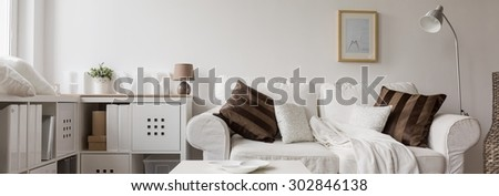 Panorama of comfortable white double sofa in modern living room - stock photo